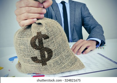 a young caucasian man wearing a gray suit seated at an office desk full of charts and financial balances holds a burlap money bag with the US dollar currency sign in his hand