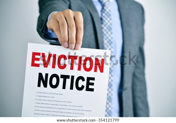 a young caucasian man wearing a gray suit shows a document with the text eviction notice