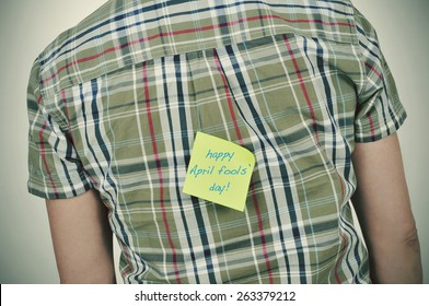 a young caucasian man wearing a plaid patterned shirt with a yellow sticky note attached to his back with the text happy april fools day written in it