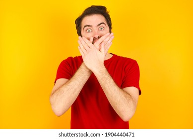 Young Caucasian man wearing red t-shirt standing against yellow background shocked covering mouth with hands for mistake. Secret concept.