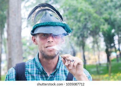 Young caucasian man wearing traditional german clothes smokes cigar in the summer park.
