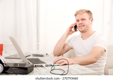 A young caucasian man working in his home office on the phone.