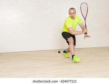 Young Caucasian man in a yellow T-shirt playing squash. Horizontal color image.