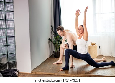 young caucasian married couple keep balance in yoga pose, stand stretching one leg in back, yoga man and woman practice yoga exercises every morning