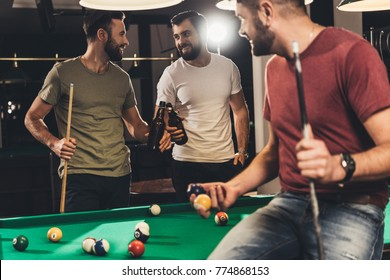young caucasian men drinking beer beside billiard table in bar