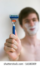 Young caucasian men holding a razor in hand in front of unfocused face