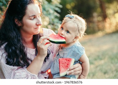 Young Caucasian mother with baby girl eating watermelon. Healthy finger food for babies. Summer sweet fruit food snack. Supplementary food for growing babies. Family picnic in park outdoors.