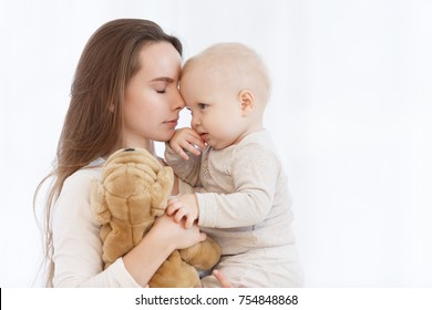 young caucasian mother holding her baby son in her arms before bedtime in a light bedroom. The family is dressed in white pajamas. Mother's Day. Mother's care and love