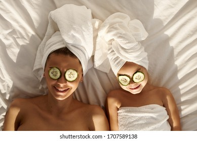 A young caucasian mother and little daughter with wrapped hair in white bath towels lying on the bed, and applying pieces of cucumber to their eyes. Family spa. Top view