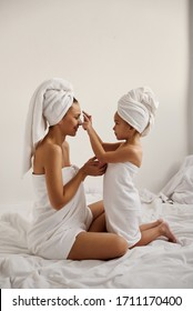 A young caucasian mother and little daughter with wrapped hair in white bath towels apply a clay mask on the mother faces