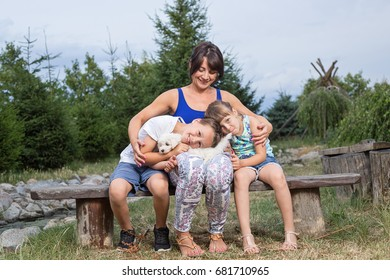 Young caucasian mother sitting outdoors in nature on summer day, hugging her two small children