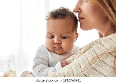 Young caucasian mum hugging cute adorable infant african american baby daughter expressing single parent love and child care. Diverse mum and adorable ethnic little kid girl bonding on Mothers day.