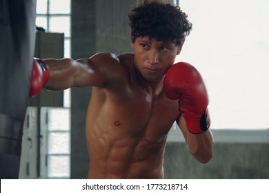 Young Caucasian muscular man making a hard punch on a punching bag with red Boxing Gloves at gym. Handsome male Boxer Training