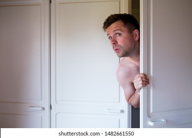 Young caucasian naked man hiding in wardrobe. Guy is afraid to be found by husband. Treason concept.