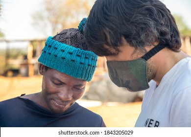 young Caucasian from an NGO collaborating with an african man in his village in Botswana