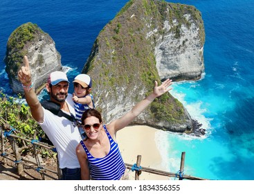 Young caucasian parents holding their two years old son with  the stunning Kelingking beach on background, on of the most amazing spots in Nusa Penida Island, Bali.
