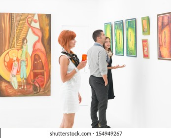young caucasian people in an art gallery looking at paintings and talking about them