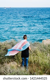 a young caucasian person, seen from behind, draping a transgender pride flag over his or her shoulders, facing the ocean