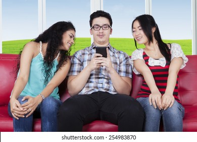 Young caucasian person typing message on the smartphone near curious women