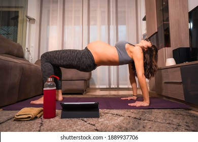 Young caucasian pregnant woman in gray t-shirt performing pilates back exercise. Online exercises in prepartum classes, wellness during pregnancy