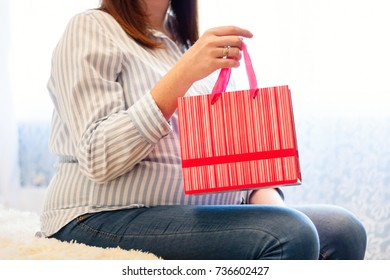 Young caucasian pregnant woman holding red shopping bag. Xmas gifts for mothers