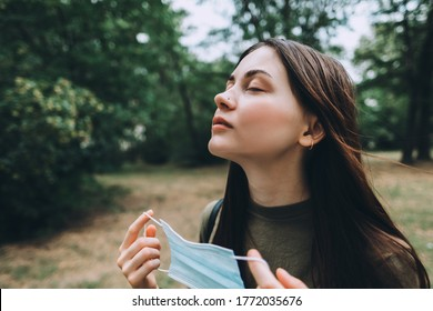 Young caucasian pretty woman removes a medical protective mask from her face on nature, surrounded by trees, breathing clean fresh air