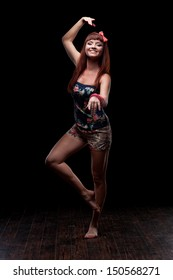 young caucasian red-haired female dancer showing move over black background