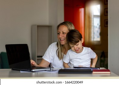 Young Caucasian single mother working on laptop while her son is using digital tablet.Mother and her son spending time together at home.Mother using laptop and her son using tablet.Technology concept.