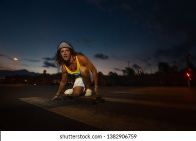 A young Caucasian skateboarder rides skateboard at night