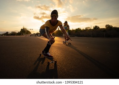 A young Caucasian skateboarder rides skateboard at sunset
