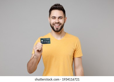 Young caucasian smiling bearded attractive handsome rich successful happy man 20s in casual yellow basic t-shirt hold credit bank card look camera isolated on grey color background studio portrait