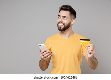 Young caucasian smiling bearded dreamful pensive student man 20s wear casual yellow basic t-shirt hold mobile cell phone credit bank card shopping online isolated on grey background studio portrait