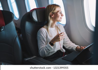 Young caucasian smiling female enjoying her comfortable flight while sitting in airplane cabin, listening to music in earphones and drinking water. Wifi internet access on board, passenger near window