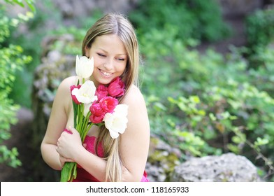 Young caucasian smiling woman and tulips outdoors at green nature background