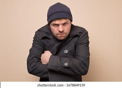 Young caucasian speculator man gangster or bandit looking angry at camera closing his coat. Studio shot