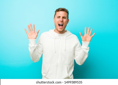 Young caucasian sport man celebrating a victory or success, he is surprised and shocked.