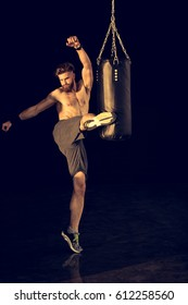 young caucasian sportsman kicking punching bag  isolated on black