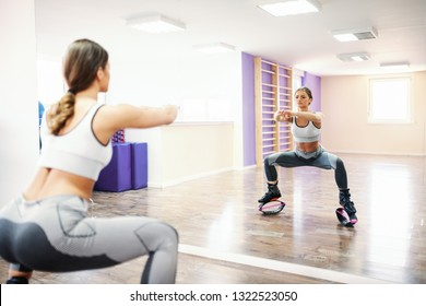 Young Caucasian sporty brunette with ponytail and in sportswear doing squaring endurance in kangoo jumps footwear in front of mirror.