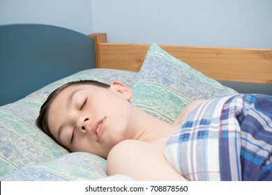 Young caucasian teenage boy asleep in his bed