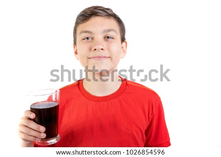 Young caucasian teenage boy drinking a glass of cola drink