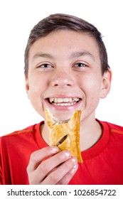 Young caucasian teenage boy eating a sausage roll