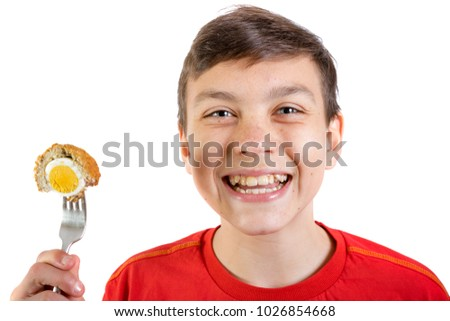 Young caucasian teenage boy eating a scotch egg