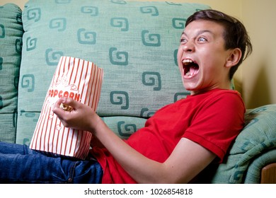 Young caucasian teenage boy watching a scary film
