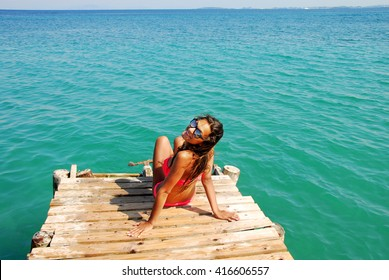 young Caucasian teenage girl on the wooden pier by blue Ionian sea, Greece