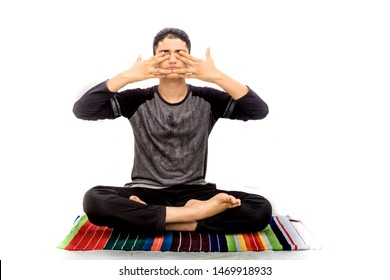 A young caucasian teenager wearing activewear pants and black colored t-shirt and performing Bhramari pranayama or human humming bee breathing exercise yoga isolated on white.On colorful yoga mat.