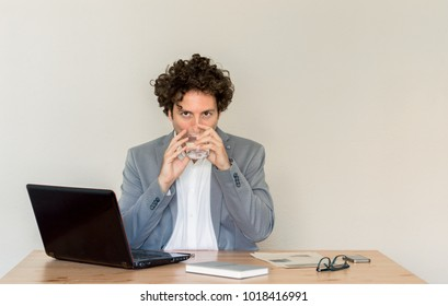 Young Caucasian, thirsty business expert sitting at his desk in front of empty clear wall