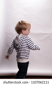 Young Caucasian Toddler Boy Acts Silly On A Photo Shoot In Front of A White Background