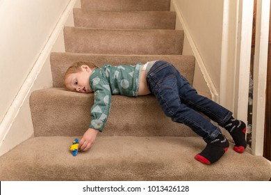 A Young Caucasian Toddler Boy Plays On A Carpeted Staircase In His Suburban Home