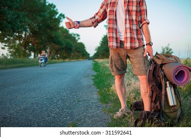Young caucasian tourist with backpack hitchhiking along a road in sunset