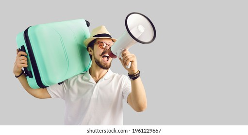 Young caucasian tourist man in summer hat with luggage suitcase on shoulder screaming on megaphone advertising great tour agency offer, sale discount. Studio portrait with copy space - Shutterstock ID 1961229667